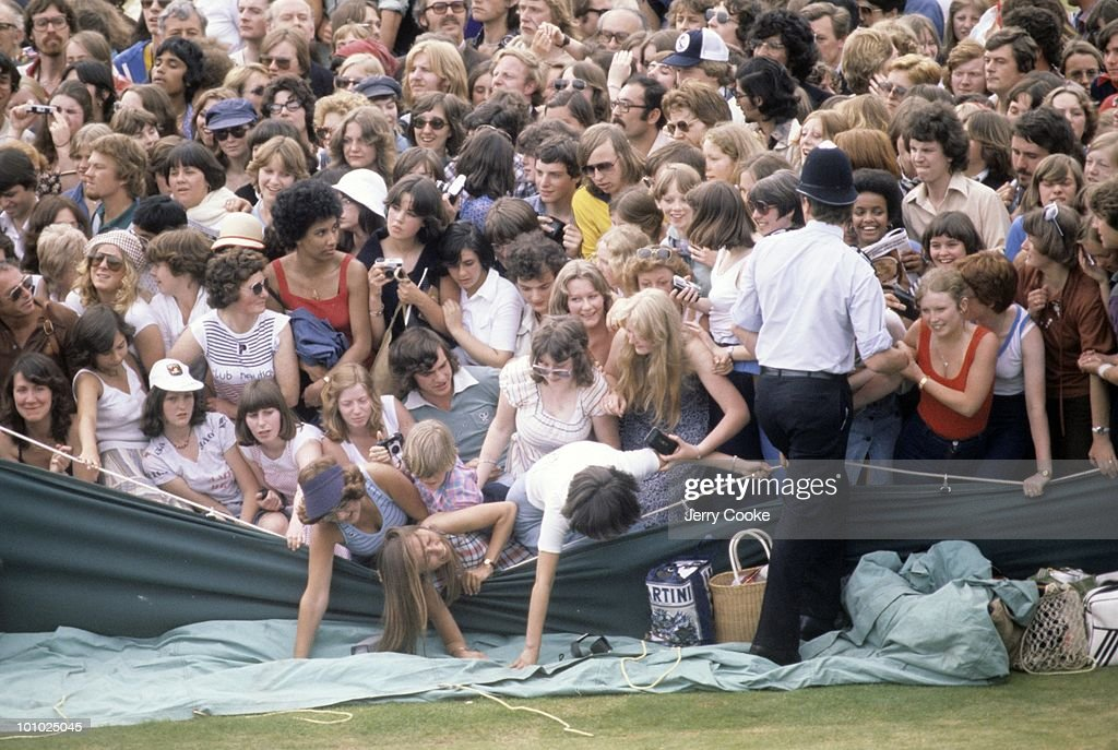 View of fans in stands falling over fence during match at All England Club. London, England 6/30/1977