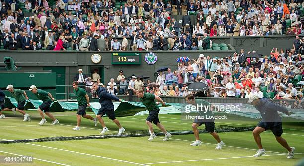 Wimbledon View of groundskeepers rolling out tarp onto Centre Court during rain delay of Men's Final match between Serbia Novak Djokovic and...