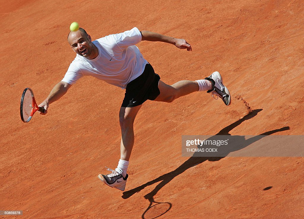 US tennisman Andre Agassi runs to hit the ball, 20 May 2004 at Roland-Garros in Paris, during a training session in preparation to this season's second Grand Slam tournament starting at Roland Garros next 24 May.