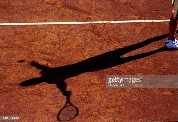 Tennisspielerin in der Aufschlagbewegung Schatten auf rotem Sandplatz