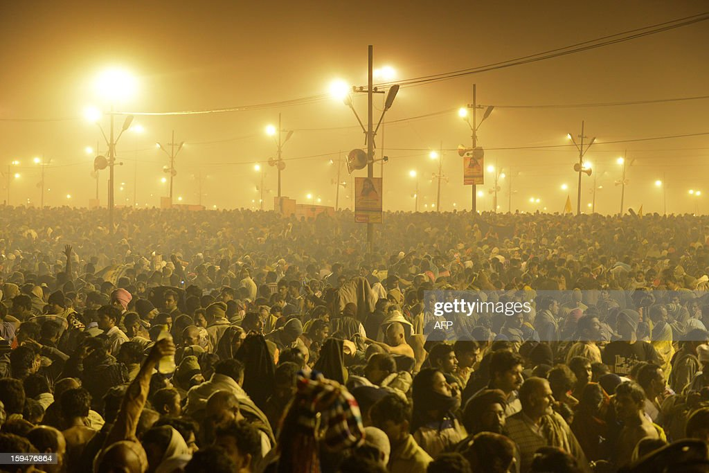 Tens of thousands of Hindu devotees crowd a large field on the banks of the Sangham or confluence of the Yamuna and Ganges rivers as they surge forward slowly and hope to take a dip in the waters during the Kumbh Mela in Allahabad on January 14, 2013. Hundreds of thousands of Hindu pilgrims led by naked, ash-covered holy men streamed into the sacred river Ganges at the start of the world's biggest religious festival. The Kumbh Mela in the Indian town of Allahabad will see up to 100 million worshippers gather over the next 55 days to take a ritual bath in the holy waters, believed to cleanse sins and bestow blessings. AFP PHOTO/ Sanjay Kanojia