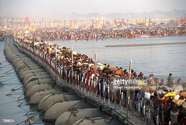Tens of thousands of Hindu pilgrims walk across pontoon bridges over the Ganges River during the Maha Kumbh Mela festival January 23 2001 in...