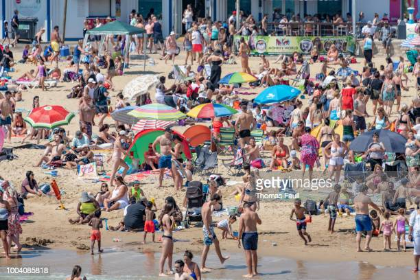 tens of thousands of people crowd the beach in bournemouth, uk - bournemouth england stock photos and pictures