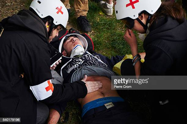 Tens of thousands of protesters attend a rally against labour reforms as a protester lays injured on the ground on June 14 2016 in Paris France...