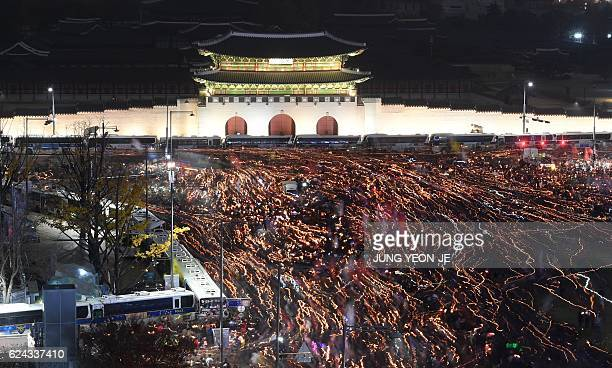 Tens of thousands of protesters holding candles march in front of Gwanghwamun the main gate to the royal Gyeongbokgung Palace of the Joseon dynasty...