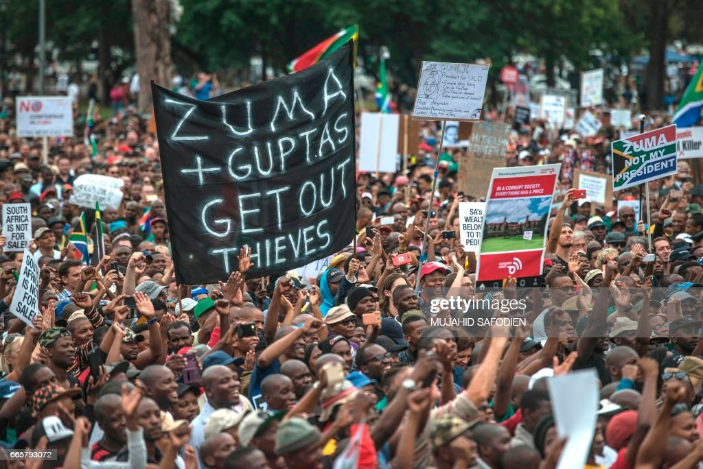 Tens of thousands of South Africans from various political and civil society groups march to the Union Buildings to protest against South African president and demand his resignation on April 7, 2017 in Pretoria. The protest comes after South African President Jacob Zuma dismissed widely respected South African Minister of finance, Pravin Gordhan in a cabinet reshuffle. The move by Zuma has caused the South African economy to be given a 'junk' rating by two of the international financial ratings agencies widely seen as a move to allow a controversial nuclear deal with Russia to go through, as well as allowing the Gupta family to buy a bank in the country, neither of which Gordhan would allow as Minister of Finance. A cut-out poster of Atul Gupta is visible. /