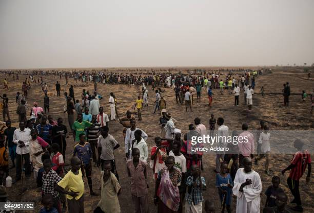 Tens of thousands of South Sudanese people line up to register for a food distribution administered by the International Committee of the Red Cross...
