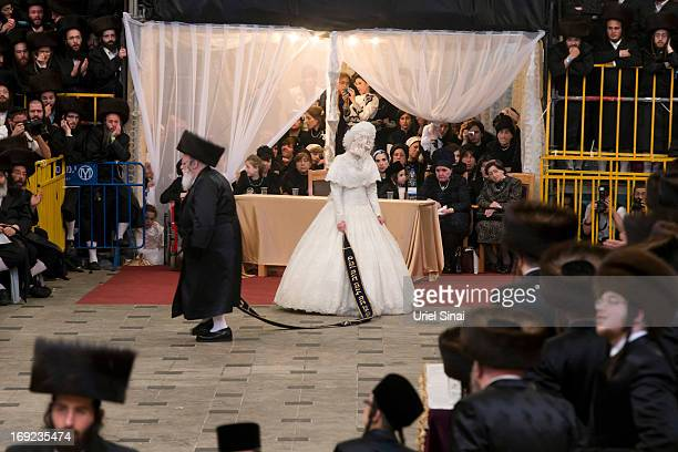 Tens of thousands of UltraOrthodox Jews of the Belz Hasidic Dynasty watch the the bride Hannah Batya Penet dances with her relative during the...