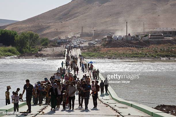 Tens of thousands of Yezidi cross a bridge from Syria back into Iraq. Tens of thousands of Yezidi--an minority ethno-religious group in Iraq--have...