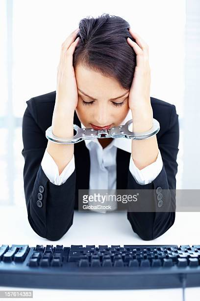 Tensed business woman tied up in handcuffs at desk