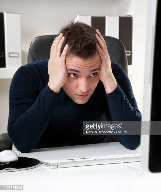 tensed businessman using computer at desk in office - benedetto photos et images de collection