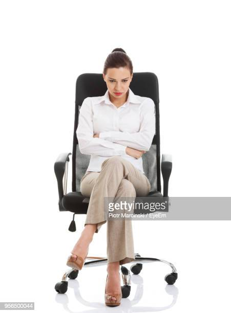 tensed businesswoman sitting against white background - uncomfortable stock pictures, royalty-free photos & images