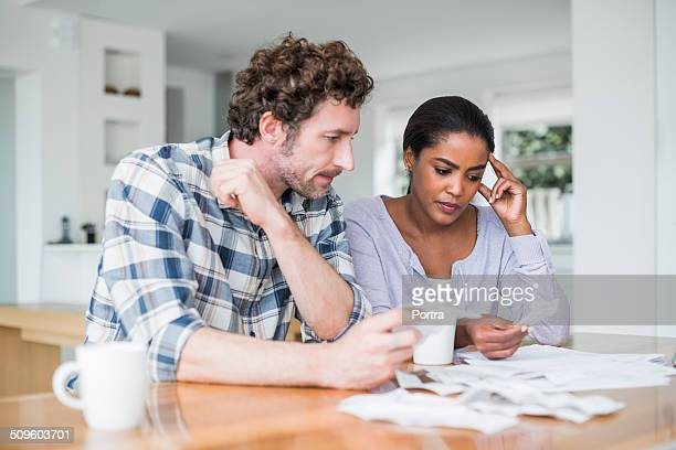 tensed couple reading bills - worried stock pictures, royalty-free photos & images