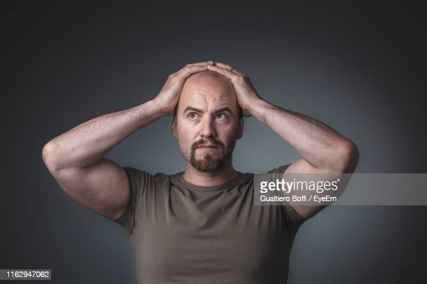 tensed man standing against gray background - head in hands stock pictures, royalty-free photos & images