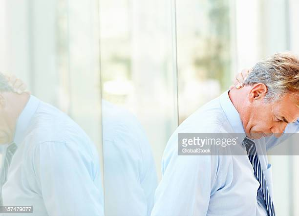 Tensed mature businessman looking down