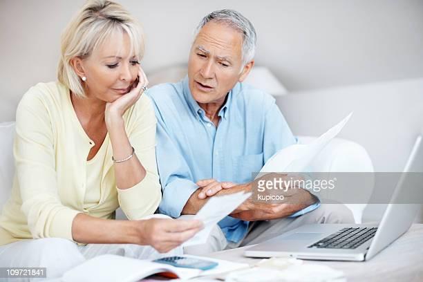 Tensed couple d'âge mûr parler de leurs dépenses mensuels à la maison