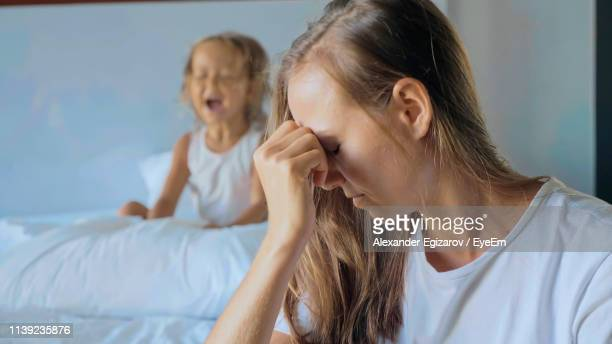 tensed mother with daughter at home - moms crying in bed stock photos and pictures
