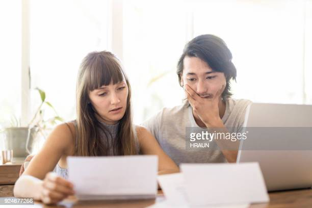 Tensed young couple reading document at home