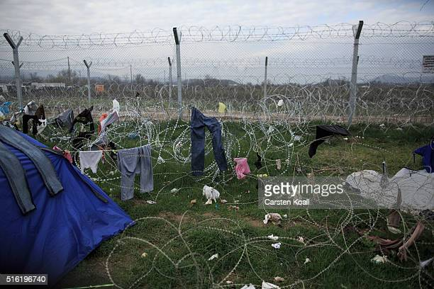 A tent and several clothes hang on a barbed wire fence limits the Greek to the Macedonian side in the Idomeni refugee camp on the Greek Macedonia...