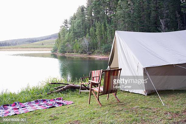 Tent, deck chairs and blanket by lake