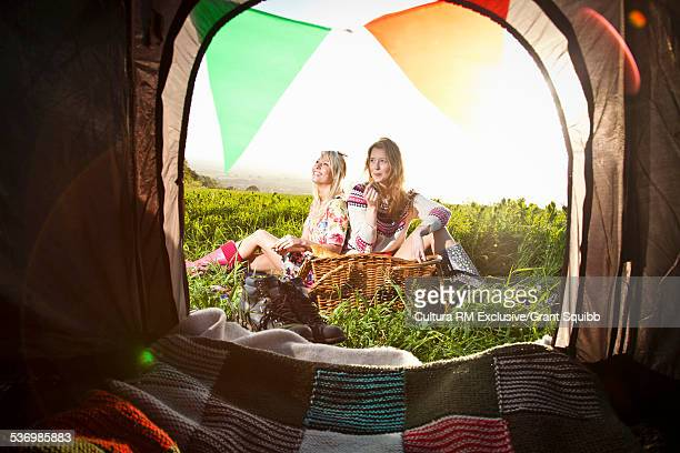 Tent entrance view of young women friends picnicing in rural field