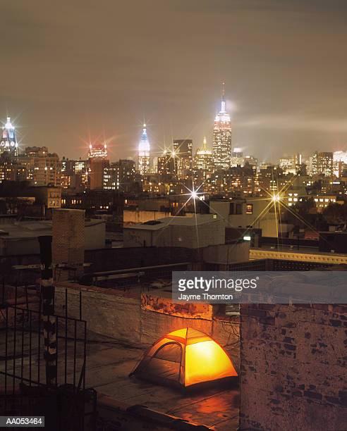 Tent illuminated on urban rooftop, night