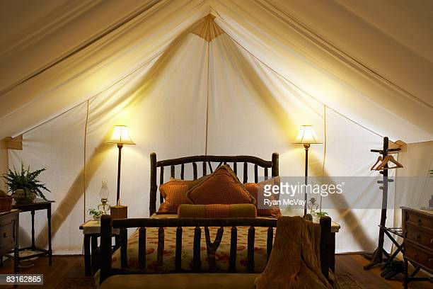 Tent interior with bed and lamps.
