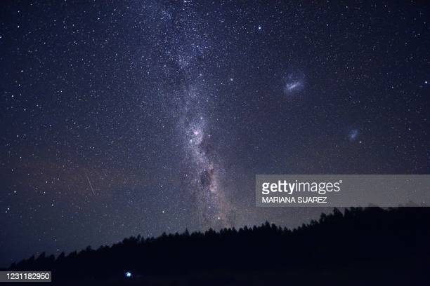 Tent is seen between trees as the Milky Way appears in the sky in the Uruguayan countryside some 185 km north of Montevideo near Capilla del Sauce,...