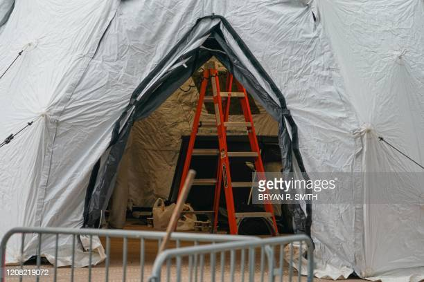 A tent is under construction as workers build a makeshift morgue outside of Bellevue Hospital to handle an expected surge in Coronavirus victims on...