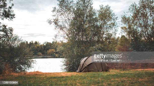 tent on field by lake against sky - milton keynes stock pictures, royalty-free photos & images