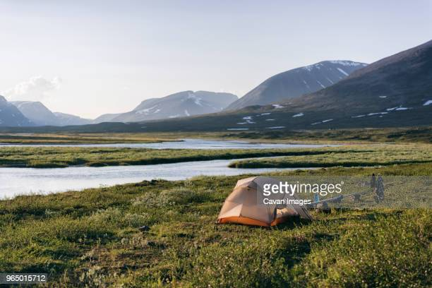 tent on field by river against mountains - norrbotten province stock photos and pictures