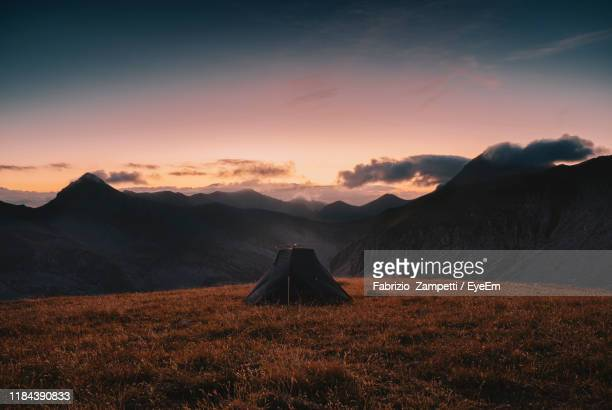 tent on land with mountains in background against sky during sunrise - fabrizio zampetti foto e immagini stock