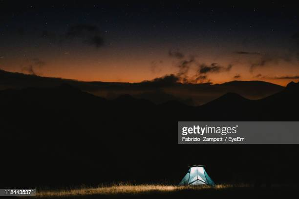 tent on mountains against cloudy sky at sunrise - fabrizio zampetti foto e immagini stock