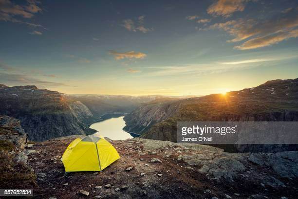 Tent on plateau overlooking fjord at sunset, Norway