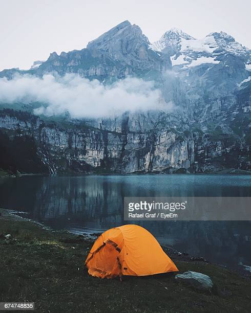 Tent On Shore By Oeschinen Lake Against Rocky Mountains At Swiss Alps