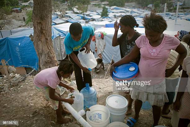 Tent residents fill water containers March 30 2010 in the Peguy Ville neighborhood of PortauPrince Haiti Many Haitians are still living in tent...