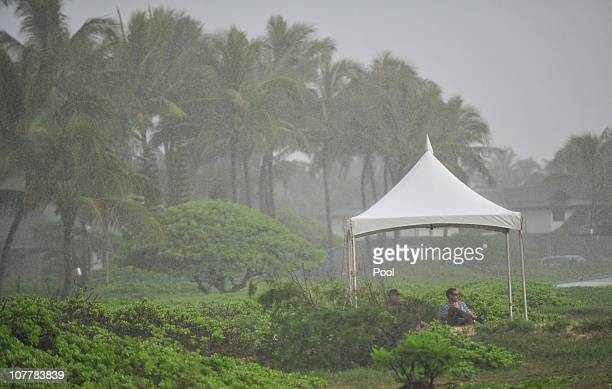 A tent shelters security personnel from rain as they sit on Kailua Beach in the area of President Obama's winter retreat on December 26 2010 in...