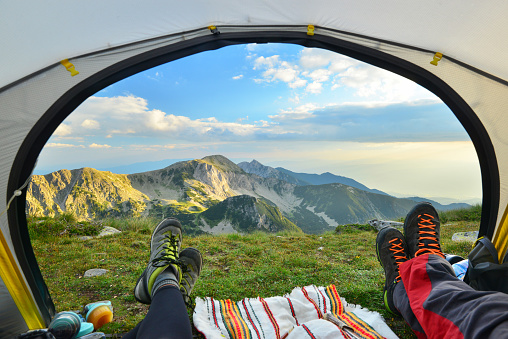 Tent view of mountain range with hiking boot in the foreground - gettyimageskorea