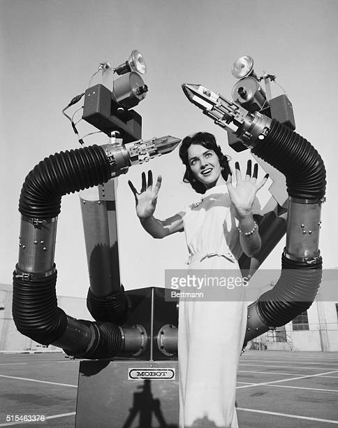 Tentaclelike arms of Mobot Mark II a mobile robot built by the Hughes Aircraft company in Culver City California close in on Colleen Adams as it...