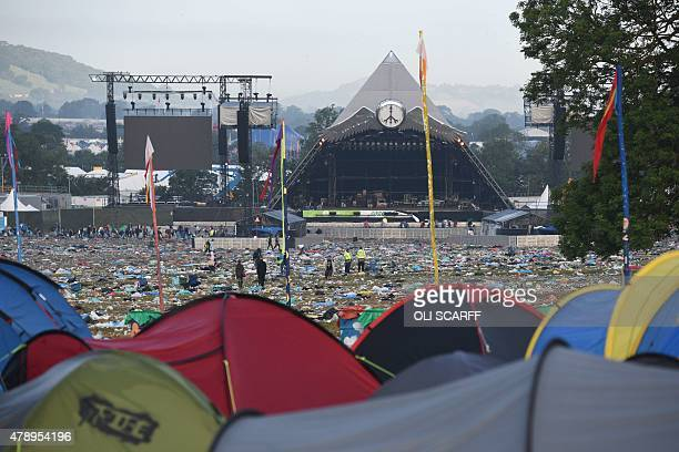 Tents are pictured against a backdrop of discarded litter at the end of the Glastonbury Festival of Music and Performing Arts on Worthy Farm near the...
