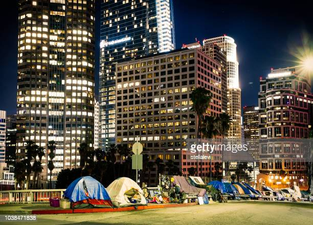 tents beside skyscrapers in los angeles downtown at night - homeless los angeles stock photos and pictures