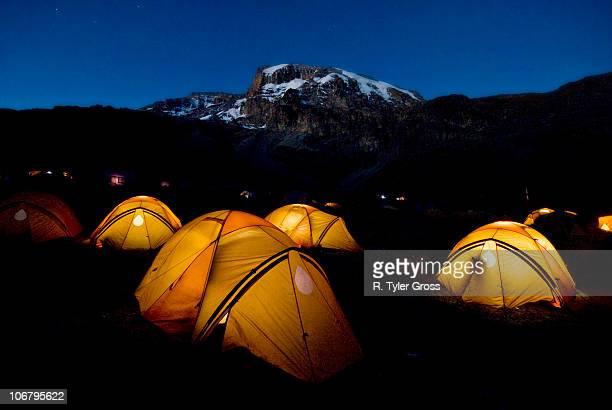 tents illuminate the night 2,000 ft. below the summit of mt. kilimanjaro. - mt kilimanjaro stockfoto's en -beelden