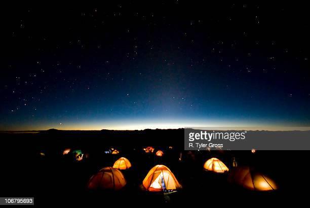 Tents illuminate the night as stars fill the sky on mMt. Kilimanjaro.