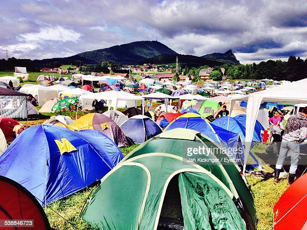 Tents On Field Against Cloudy Sky