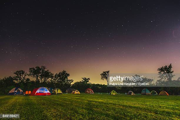 Tents On Grassy Field Against Star Field At Night