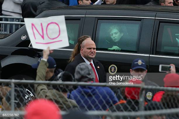 Tenyearold Barron Trump looks out the window of the presidential limosouine as he joins his parents US President Donald J Trump and first lady...