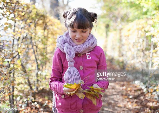 ten-year-old girl marveling at colorful leaves