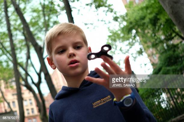 Tenyearold Louis Wuestenberg plays with a fidget spinner in a park in New York on May 23 2017 It was supposed to calm nerves relieve stress and...