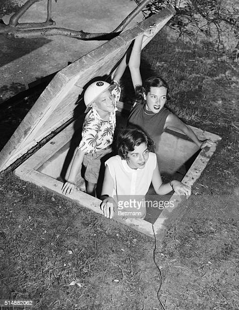 Tenyearold Mitchell Legler his sister Sandra and her friend Nancy Walker test the escape hatch of the Legler family's bomb shelter in Bronxville New...