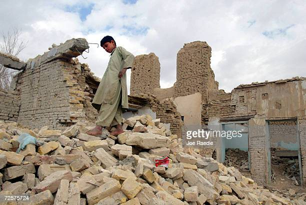 Tenyearold Nasir Ahmad walks on the rubble of a house February 21 2002 that was destroyed by an American bombing run in the city of Kandahar...